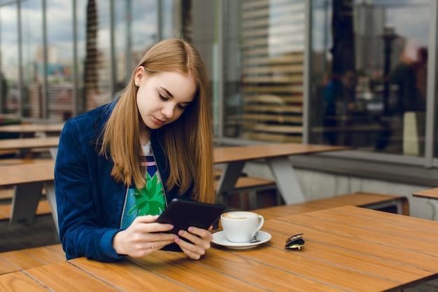 Ein hübsches mädchen mit langen haaren sitzt am tisch auf der terrasse in der stadt. sie arbeitet an dem tablet.