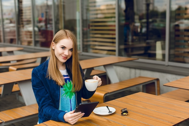 Ein hübsches mädchen sitzt am tisch auf der terrasse. sie hält eine tasse kaffee und eine tablette. sie lächelt in die kamera.