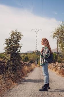 Ein hübsches modell posiert für ein foto, das von der seite eines pfades schaut