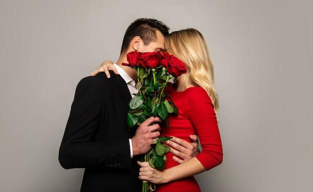 Ein hübsches paar in schicken outfits versteckt sich beim küssen und umarmen hinter einem wunderschönen strauß roter rosen.
