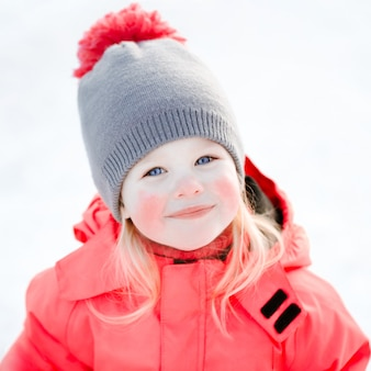 Ein hübsches weißes mädchen in einer gestrickten wintermütze und einem rosa overall, lächelnd und lachend im schnee