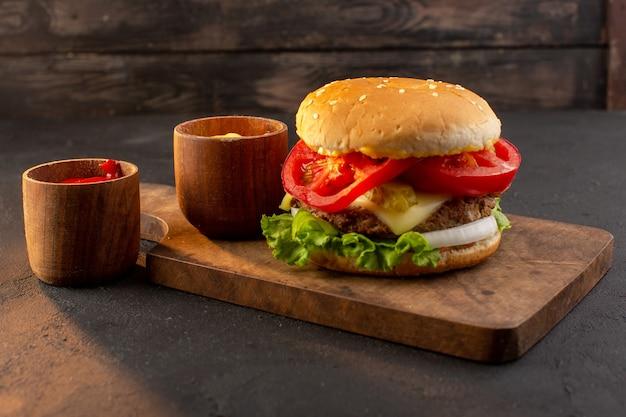 Ein hühnchen-burger mit käse und grünem salat von vorne auf dem holzschreibtisch und sandwich-fast-food-mahlzeit