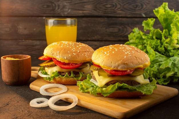 Ein hühnchen-burger von vorne mit käsesaft und grünem salat auf dem holzschreibtisch und sandwich-fast-food-mahlzeit