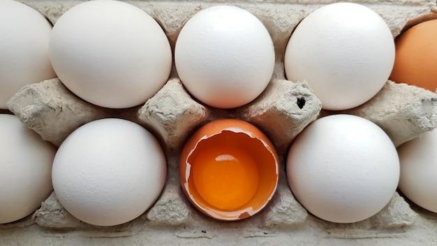 Ein hühnerei ist unter anderen eiern halb zerbrochen. nahaufnahmen in einem papierfach zur aufbewahrung.