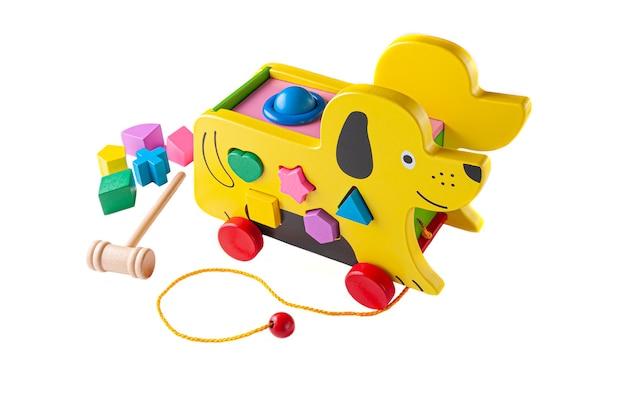 Ein hund aus holz an einem seil. sortier- und hammerspiel für kinder. lernspielzeug montessori 3 in 1. weißer hintergrund. nahansicht.