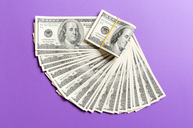 Ein hundert-dollar-währungsfanabschluß oben, draufsicht des geschäftskonzeptes auf farbigem hintergrund mit kopienraum