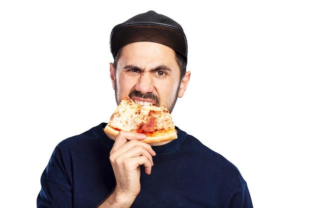 Ein hungriger mann mit mütze isst vor appetit ein stück pizza. isoliert auf weißem hintergrund.