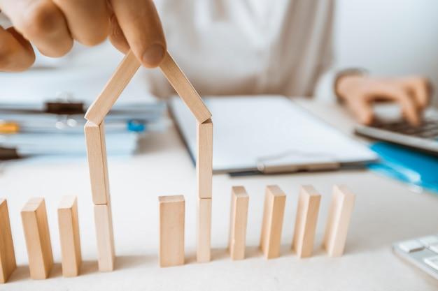Ein immobilienmakler hält einen teil des grundrisses des hauses in der hand.