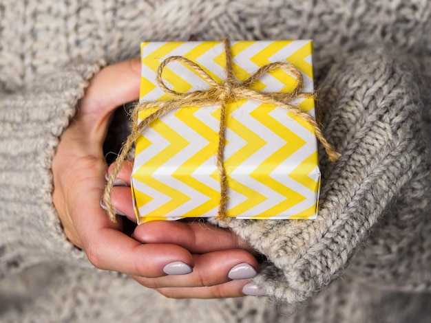 Ein in gelbes papier gewickeltes geschenk liegt in den händen der frau