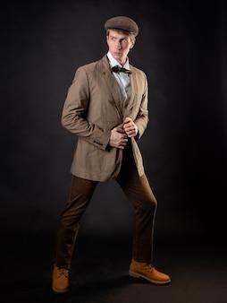 Ein intelligenter gentleman im viktorianischen stil. vintage retro-anzug, junger attraktiver mann in weste und fliege, mit einer mütze auf dem kopf