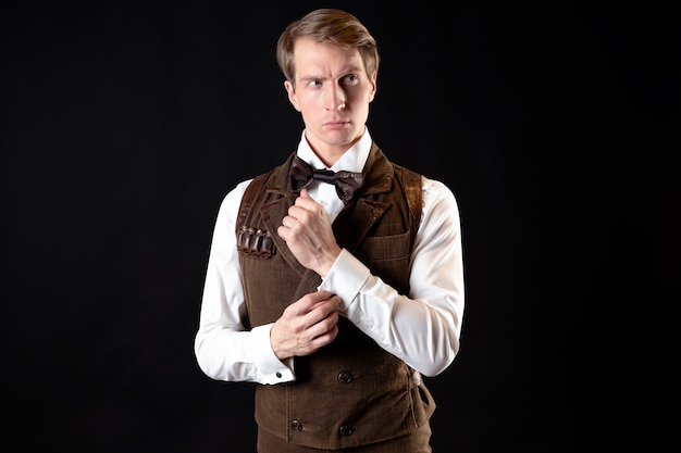 Ein intelligenter gentleman im viktorianischen stil. vintage retro-anzug, junger attraktiver mann in weste und fliege