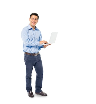 Ein intelligenter zufälliger mann steht bei der verwendung seines laptops