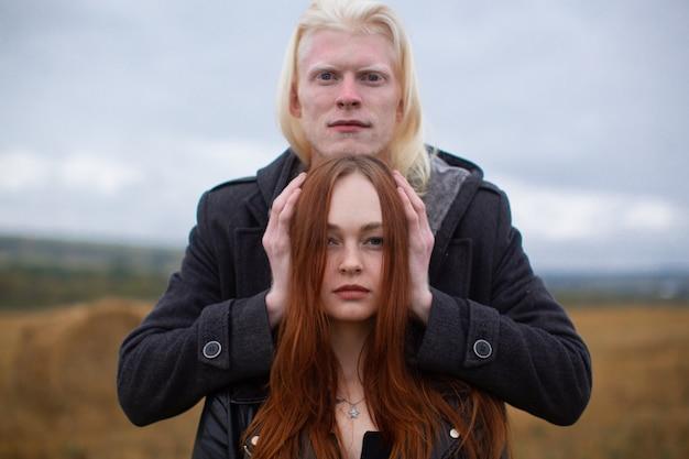 Ein interessanter albino-typ steht in der nähe eines rothaarigen mädchens mitten auf einem feld und hält ihren kopf mit seinen händen. junges verliebtes paar. hochwertiges foto