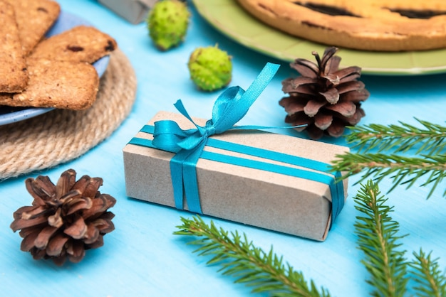 Ein interessantes weihnachtsgeschenk, umgeben von köstlichen keksen und beerenkuchen.