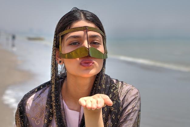 Ein iranisches mädchen im hijab und traditionelle maske der muslime im südlichen iran sendet einen luftkuss, bander abbas, hormozgan.