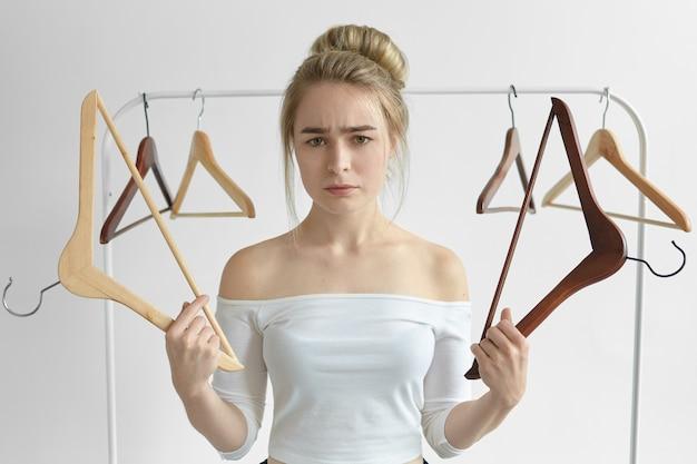 Ein isolierter schuss einer frustrierten, verärgerten jungen frau in einem weißen oberteil, die leere gestelle hält, weiß nicht, was sie am datum anziehen soll, und hat einen unglücklichen blick. menschen, lifestyle, garderobe, kleidung und modekonzept