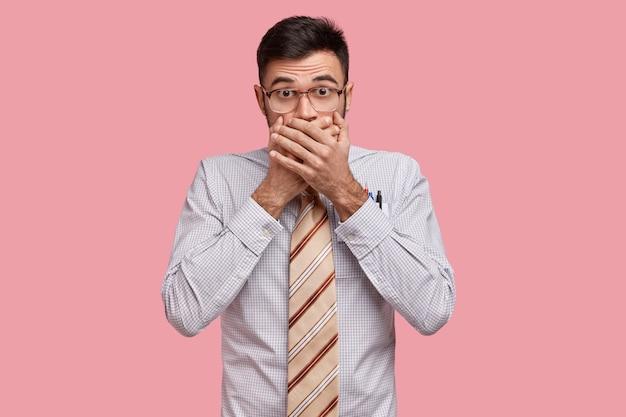 Ein isolierter schuss eines verblüfften, gutaussehenden unternehmers bedeckt den mund, ist sprachlos, verbirgt ein geheimnis, überrascht von schockierenden nachrichten
