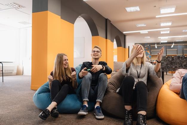 Ein it-team spielen sie videospiele auf der konsole, während sie sich nach der arbeit entspannen