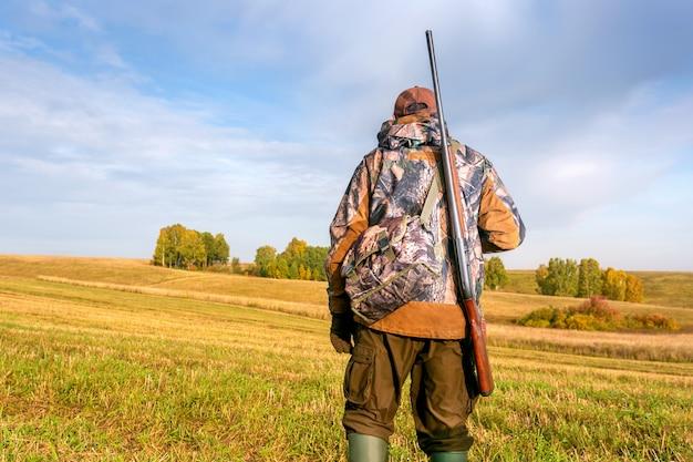 Ein jäger mit einer jagdwaffe und einer jagdform, um in einem herbstlichen wald oder feld zu jagen.