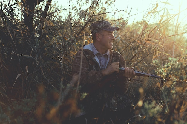 Ein jäger mit einer waffe in der hand in jagdkleidung im herbstwald auf der suche nach einer trophäe