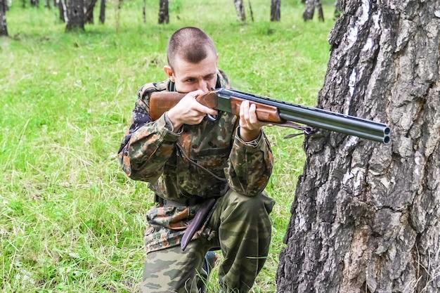 Ein jäger zielt mit einem gewehr auf ein wildes tier auf einer frühlingsjagd