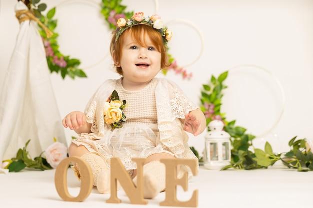 Ein jähriges baby feiert geburtstag in buchstaben eins auf weißer wand mit blumen