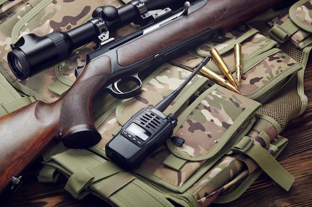 Ein jagdgewehr, munition und ein walkie-talkie liegen auf einer tarnweste auf einem tisch