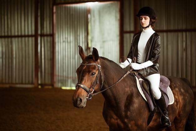 Ein jockey-mädchen in voller kleidung sitzt auf einem pferd.