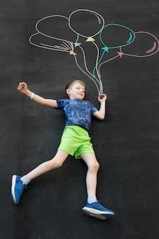 Ein junge auf dem asphalt mit luftballons. gemaltes bild von luftballons
