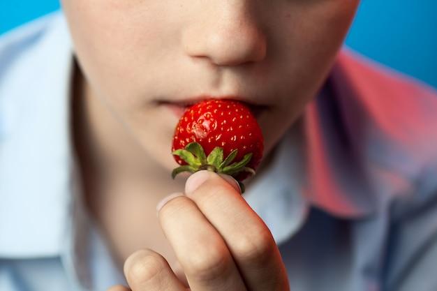 Ein junge beißt rote erdbeeren