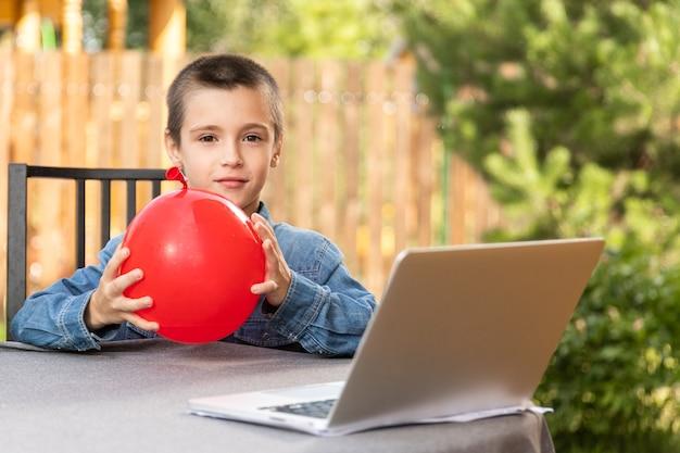 Ein junge bläst an einem warmen sommertag im garten einen roten ballon auf. geburtstagsvorbereitung