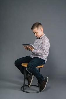 Ein junge, der auf dem schemel betrachtet digitale tablette gegen grauen hintergrund sitzt
