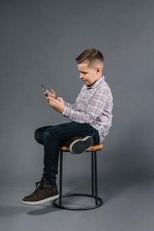 Ein junge, der auf schemel unter verwendung des handys gegen grauen hintergrund sitzt