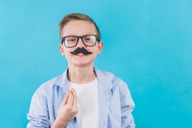 Ein junge, der die schwarzen brillen trägt, die schwarze schnurrbartstütze vor seinen oberen lippen halten