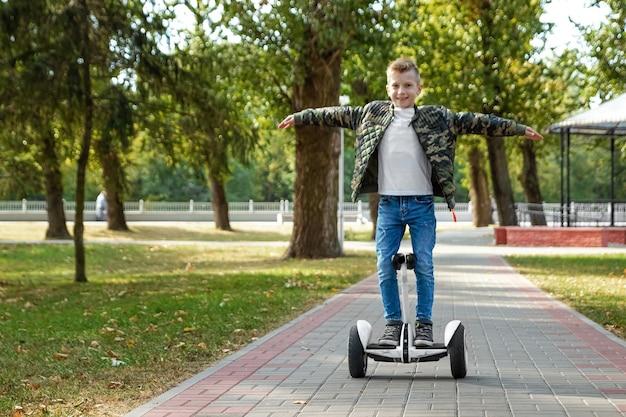 Ein junge, der ein hoverboard im park reitet