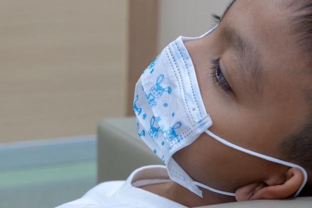 Ein junge, der eine maske zum schutz vor krankheiten trägt, weil er an einer infektion leidet
