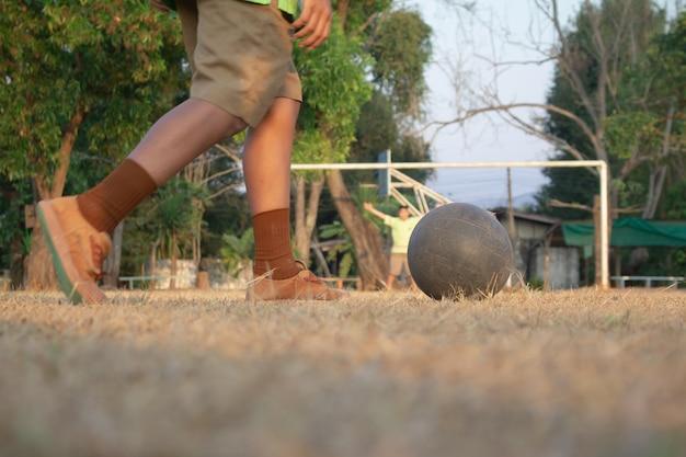 Ein junge, der fußball auf sportfeld tritt. fußballfußballtraining für kinder