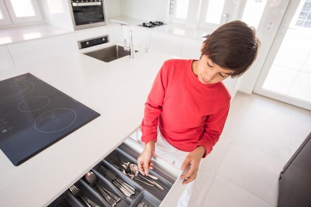 Ein junge, der in der neuen modernen küche steht