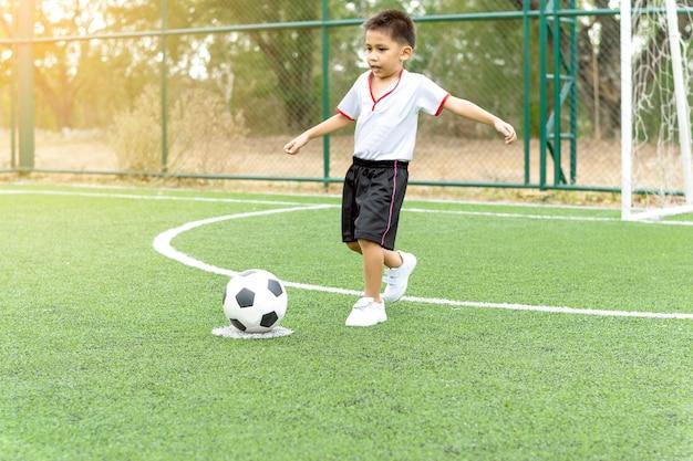 Ein junge, der läuft, um einen fußball auf dem fußballplatz zu treten.