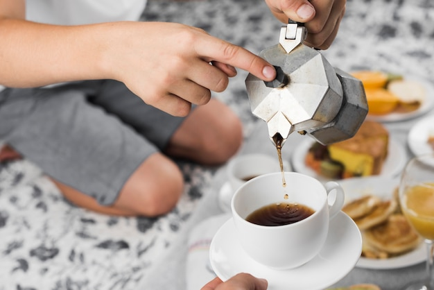 Ein junge, der schwarzen kaffee in eine schale für andere person auf frühstück gießt
