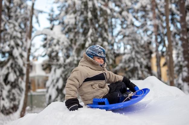 Ein junge, der sich darauf vorbereitet, auf einer untertasse den hügel hinunterzugehen winterspaß und gesunde dinge zu tun