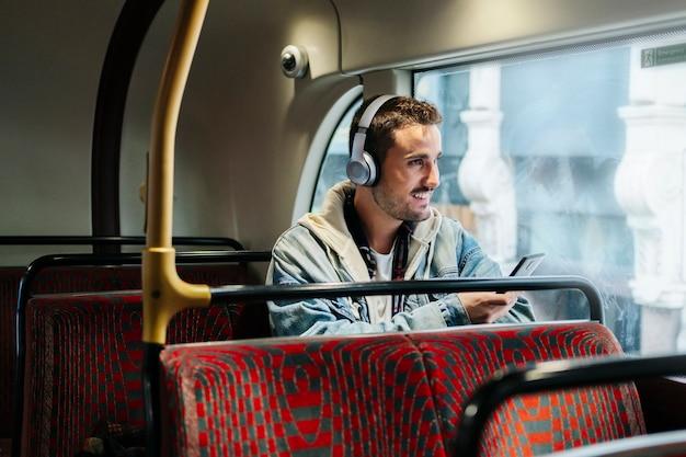 Ein junge hört musik in kopfhörern und benutzt das handy in einem bus