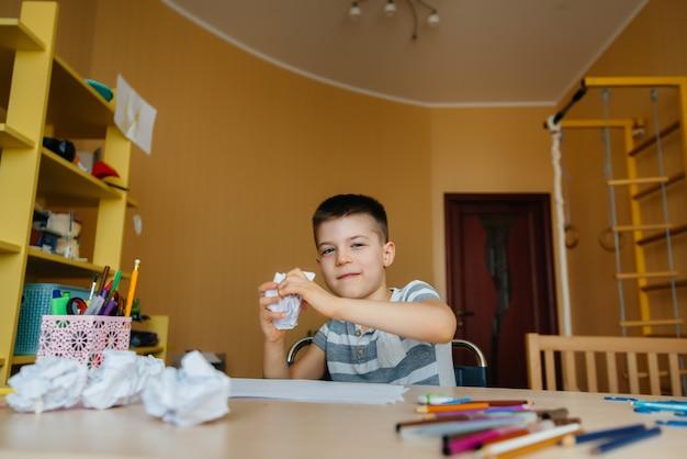 Ein junge im schulpflichtigen alter macht zu hause hausaufgaben. ausbildung in der schule.