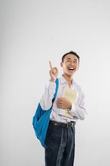 Ein junge in der uniform der junior high school, der mit dem finger nach oben schaut, wenn er ein buch und einen rücken trägt...