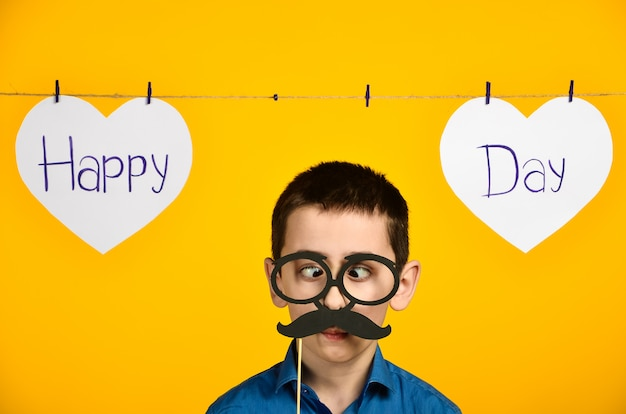 Ein junge in einem blauen hemd auf einem gelben hintergrund mit einem herzen und einer inschrift eines festlichen tages ist krumm und kleidet brille und einen schnurrbart