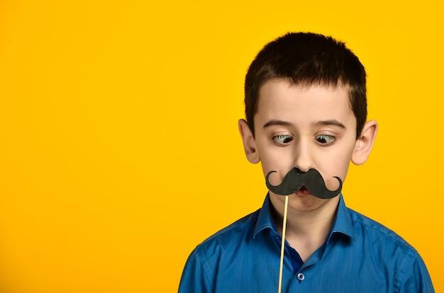 Ein junge in einem blauen hemd auf gelbem grund ist verdreht und zieht seinen schnurrbart an