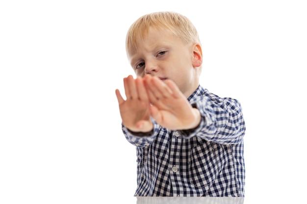 Ein junge in einem blauen karierten hemd legte die hände nach vorne. auf weißer wand isoliert. platz für text.