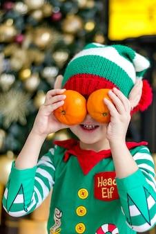 Ein junge in einem elfenkostüm mit mandarinen am weihnachtsbaum wartet auf weihnachten