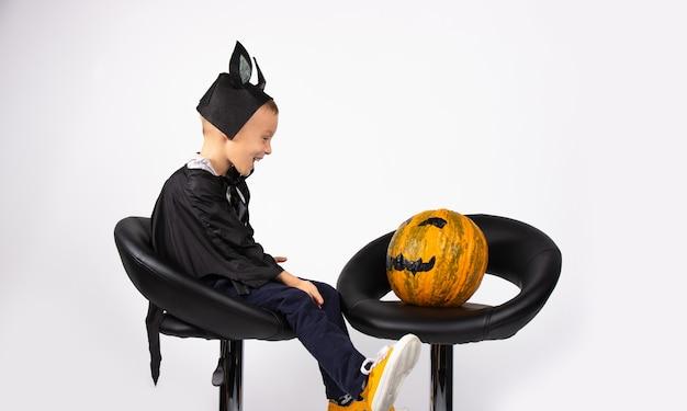 Ein junge in einem fledermauskostüm sitzt auf schwarzen stühlen mit einem kürbis. als er es neben sich sieht, lächelt er glücklich.