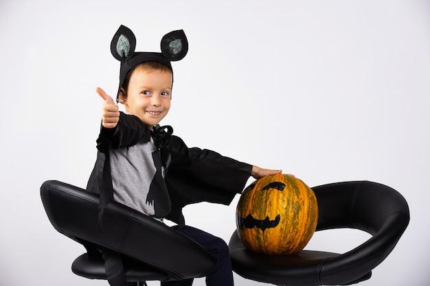 Ein junge in einem fledermauskostüm sitzt auf schwarzen stühlen mit einem kürbis. süßes oder saures, halloween-komposition.